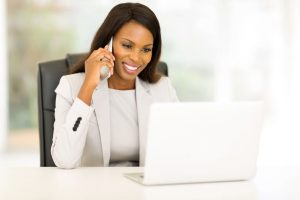 38337158 - happy african american businesswoman talking on cell phone in the office